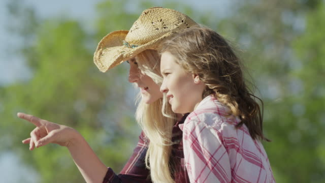 close up of woman and girl sitting on fence and talking / lehi, utah, united states - lehi stock videos & royalty-free footage