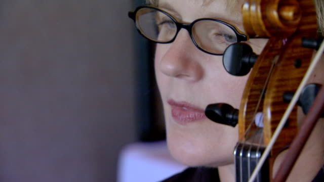 Close up of woman and top of instrument, handheld shot