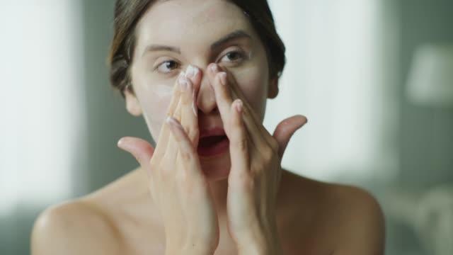 vídeos y material grabado en eventos de stock de close up of woman applying moisturizer to face in mirror / cedar hills, utah, united states - frotar