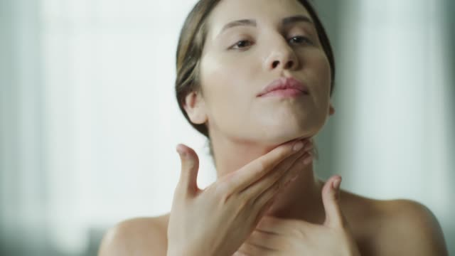 close up of woman applying moisturizer to neck and shoulders in mirror / cedar hills, utah, united states - neck stock videos & royalty-free footage