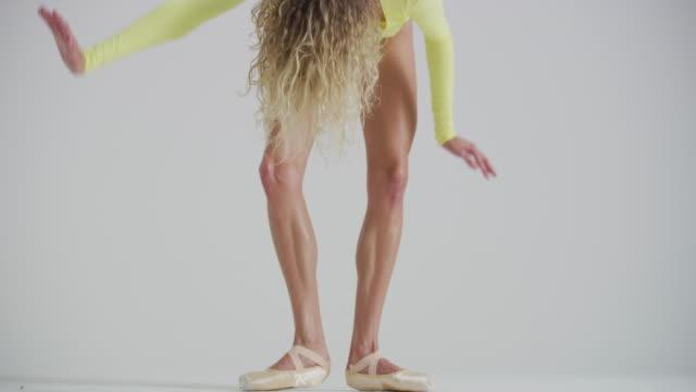 vídeos y material grabado en eventos de stock de close up of woman ballet dancer dancing, practicing, and warming up in studio - de puntas