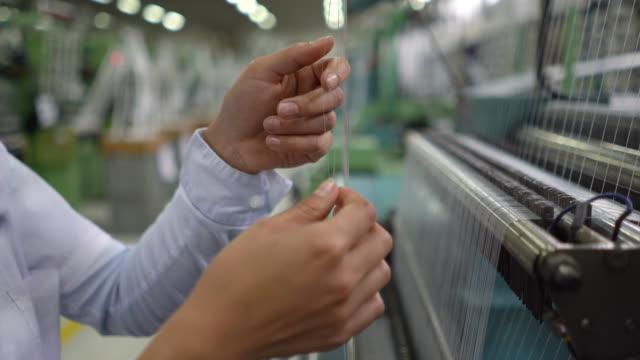 vídeos de stock e filmes b-roll de close up of woman checking rubber threads on machine at a factory - borracha material de escritório