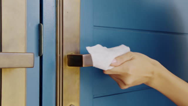 close up of woman cleaning her house front door with disinfect wet tissue wipe. - wet wipe stock videos & royalty-free footage