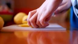 Close up of woman cutting potato
