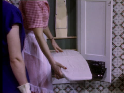 close up of woman demonstrating fold-out ironing board / 1950's - bügelbrett stock-videos und b-roll-filmmaterial