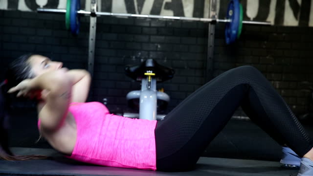 vídeos de stock e filmes b-roll de close up of woman doing sit-ups in gym - abdominais