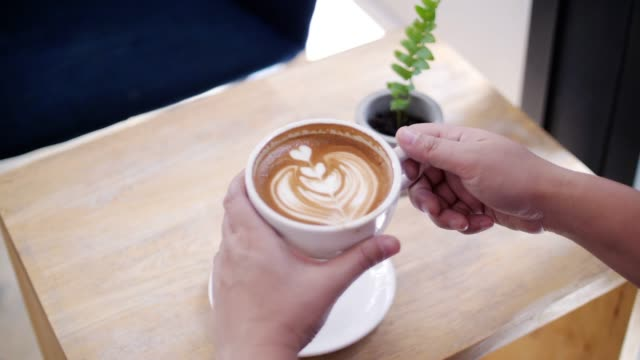 close up of woman drinking latte art coffee at cafe , slow motion - latte stock videos and b-roll footage