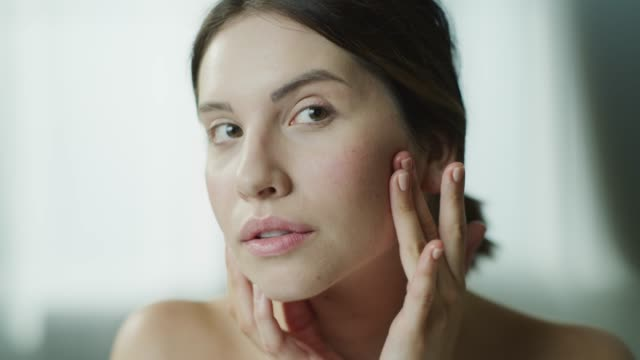 vidéos et rushes de close up of woman examining skin of face in mirror then leaving / cedar hills, utah, united states - beauté