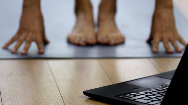 close up of woman exercising at home with laptop and remote connection - pilates stock videos & royalty-free footage