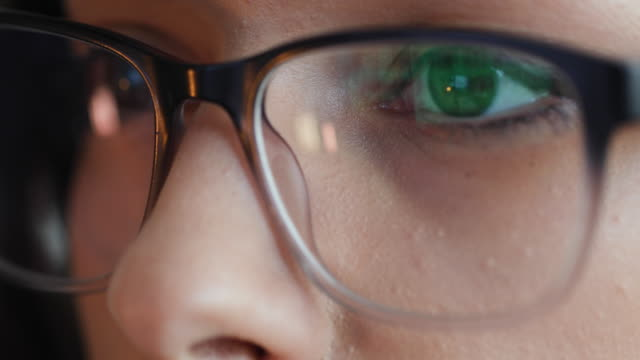 close up of woman eyes with reading glasses while working - determinazione video stock e b–roll