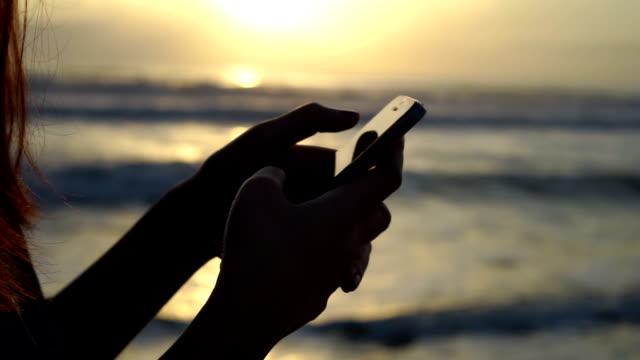 Närbild av kvinna hand använda smartphone på stranden