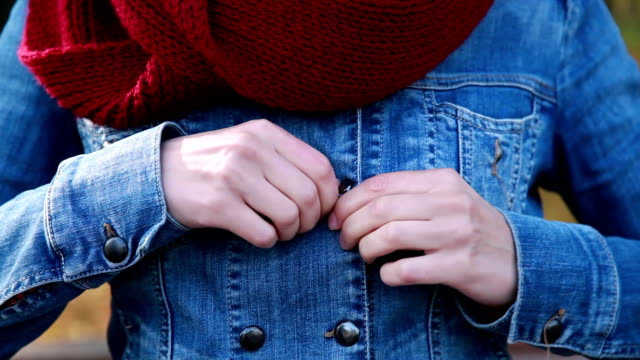 Close up of woman hands unbuttoning jacket