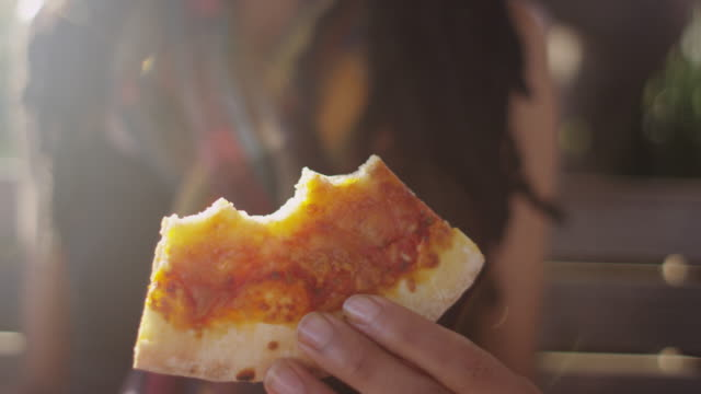Close up of woman holding a slice of pizza in her hand and taking a bite