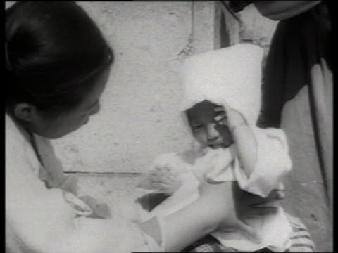 b/w close up of woman holding baby in bonnet / korea / no - korea stock-videos und b-roll-filmmaterial