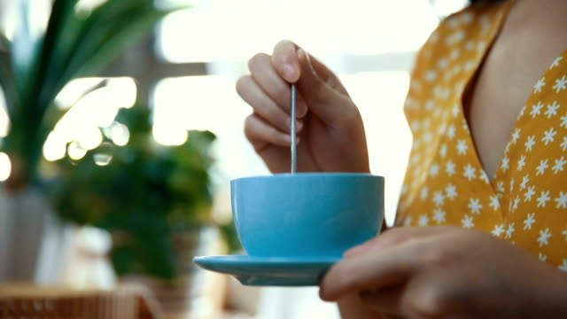 close up of woman holding coffee spoon to stir hot coffee - stirring stock videos & royalty-free footage