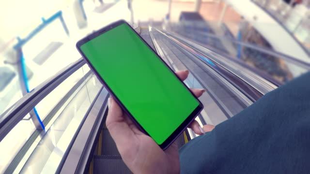 vídeos de stock, filmes e b-roll de close-up da mulher possui um smartphone com tela verde em shopping center - mercado espaço de venda no varejo