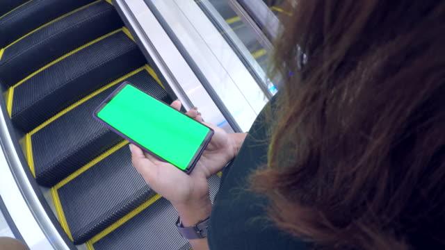 vídeos de stock, filmes e b-roll de close-up da mulher possui um smartphone com tela verde - mercado espaço de venda no varejo