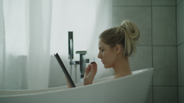 close up of woman in bathtub eating chocolate and reading digital tablet / lehi, utah, united states - vasca da bagno video stock e b–roll