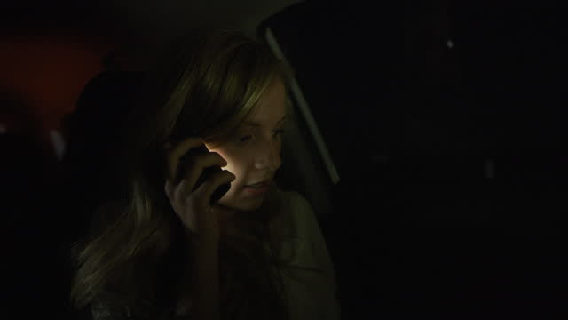 close up of woman in car at night talking on cell phone / nephi, utah, united states - 電話を切る点の映像素材/bロール