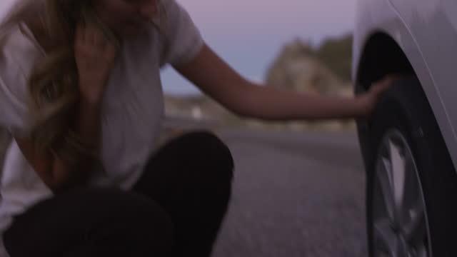 vidéos et rushes de close up of woman inspecting flat tire on car at night / nephi, utah, united states - plat