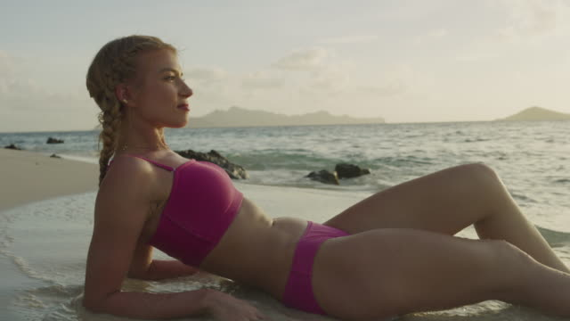 close up of woman laying on beach relaxing at sunset in ocean waves / jamesby island, tobago cays, st. vincent and the grenadines - ausgefranst stock-videos und b-roll-filmmaterial
