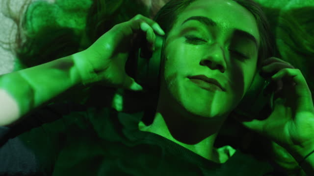 close up of woman laying on floor listening to headphones illuminated by flowing colors / cedar hills, utah, united states - herunterladen stock-videos und b-roll-filmmaterial