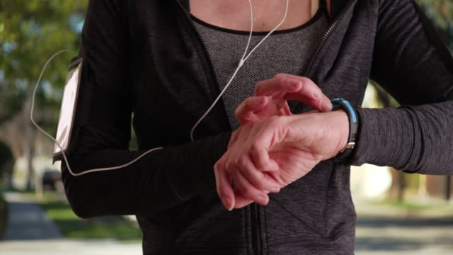 close up of woman lifting up arm to use smart watch after jog outdoors - menschliche gliedmaßen stock-videos und b-roll-filmmaterial