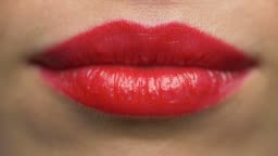 close up of woman lips with red lipstick making kissing
