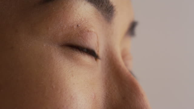 close up of woman looking away - braune augen stock-videos und b-roll-filmmaterial