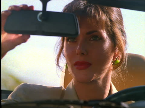 close up of woman looking in rearview mirror in convertible - 1997 stock-videos und b-roll-filmmaterial