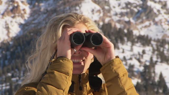 Close up of woman looking through binoculars / Blaine County, Idaho, United States