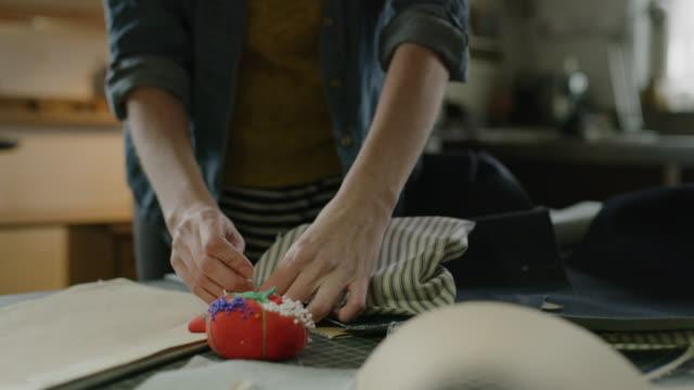 vidéos et rushes de close up of woman pinning fabric in workshop / provo, utah, united states - une seule femme d'âge mûr