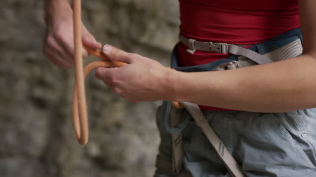 vídeos y material grabado en eventos de stock de close up of woman rock climber fastening rope to harness / american fork canyon, utah, united states - arnés de seguridad