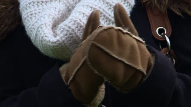 vídeos de stock, filmes e b-roll de close up of woman rubbing her gloves together - roupa quente