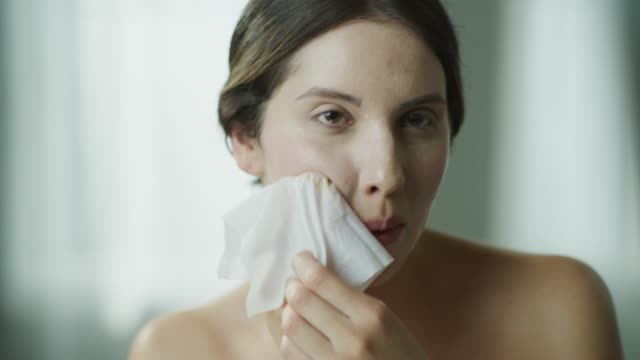 close up of woman rubbing moisturizer on face with washcloth in mirror / cedar hills, utah, united states - removing stock videos & royalty-free footage