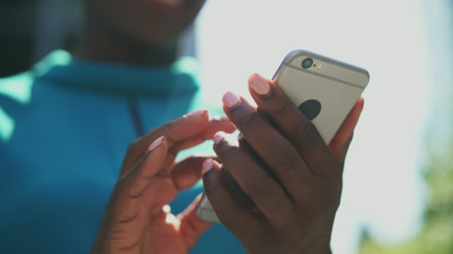 close up of woman scrolling and messaging on smart phone - usare il telefono video stock e b–roll