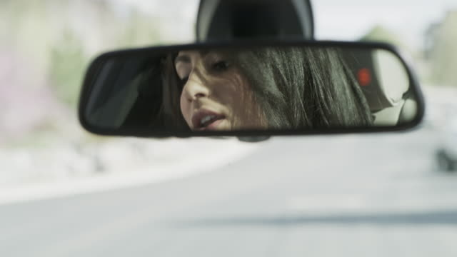 close up of woman singing in car mirror / cedar hills, utah, united states - バックミラー点の映像素材/bロール