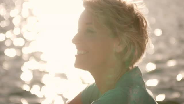 vídeos y material grabado en eventos de stock de close up of woman sitting by lake. - 50 54 años