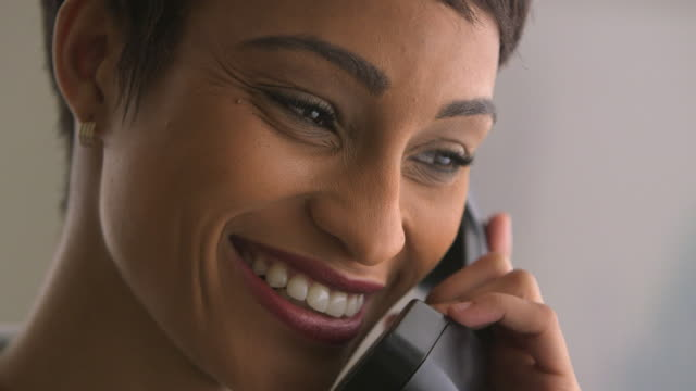 stockvideo's en b-roll-footage met close up of woman smiling and talking on phone - telefoonhoorn