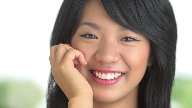stockvideo's en b-roll-footage met close up of woman smiling with hand on cheek - natuurlijk haar
