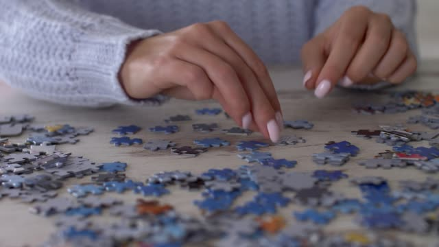 close up of woman solving a jigsaw puzzle with abundance of pieces - puzzle stock videos & royalty-free footage