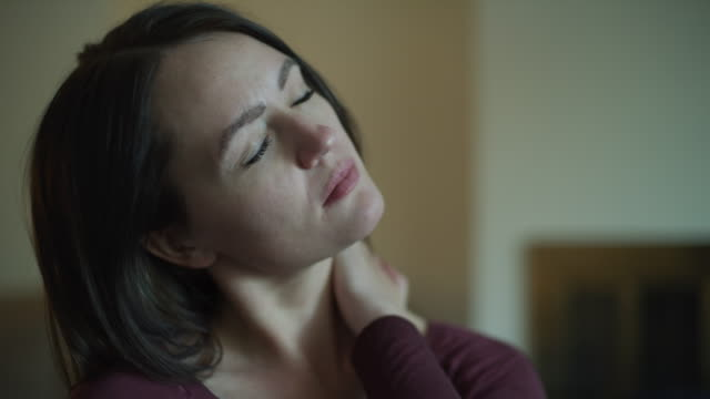 close up of woman suffering from headache and neck pain / murray, utah, united states - neckache stock videos & royalty-free footage