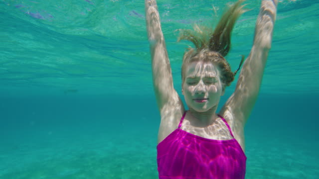 close up of woman swimming underwater in ocean then surfacing / tobago cays, saint vincent and the grenadines - surfacing stock videos & royalty-free footage