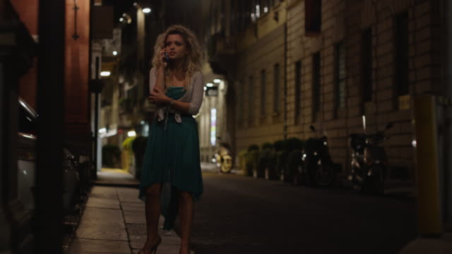 close up of woman talking on cell phone at night / milan, italy - taxi video stock e b–roll