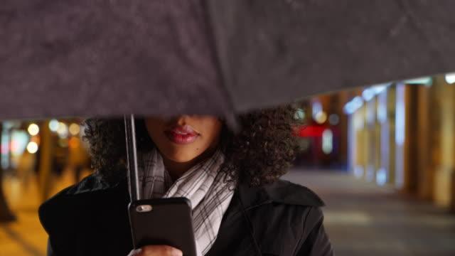 close up of woman text messaging on smartphone under umbrella on street at night - ビジカジ点の映像素材/bロール