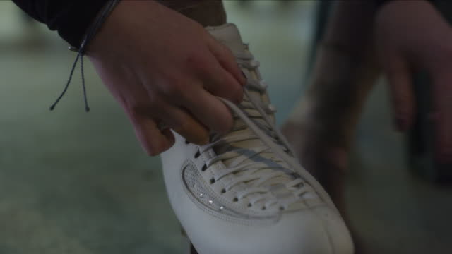 close up of woman tying shoelace on ice skate / murray, utah, united states - figure skating stock videos & royalty-free footage
