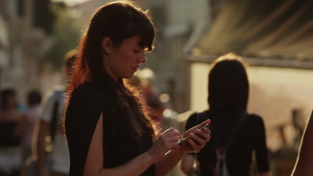 Close up of woman using cell phone / Venice, Italy