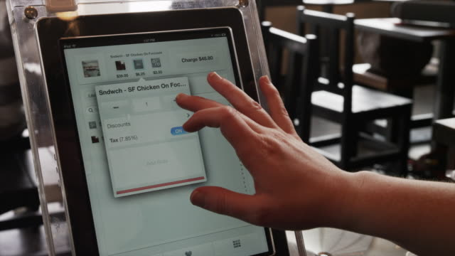 vídeos de stock e filmes b-roll de close up of woman using digital tablet ordering system in restaurant / orem, utah, united states,  - orem
