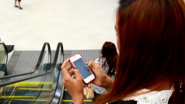 Close up of Woman Using Mobile Smart Phone in Shopping Mall