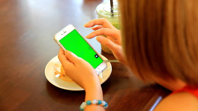 Close up of Woman Using Mobile Smartphone in restaurants.